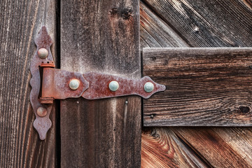 Old rusty hinge on wooden weathered door