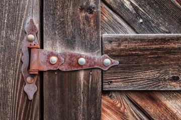 Old rusty hinge on wooden weathered door