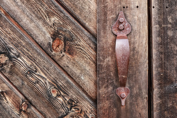 Old rusty metal handle on wooden weathered door