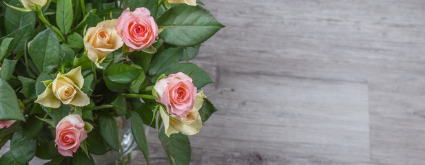 Pink and yellow roses bouquet over wooden table
