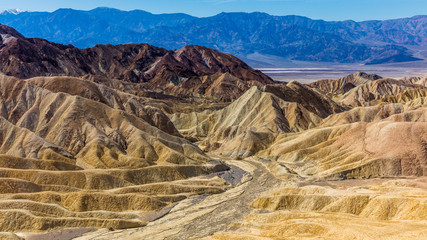 Erosional landscape of hills composed of sediments from Furnace Creek Lake, which dried up 5 million years ago. Wide view of landscape sand dunes. Beautiful view over Zabriskie point, Death Valley