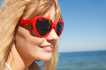 Girl in red sunglasses relaxing on sea coast.