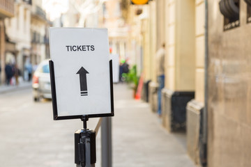 Sign and arrow for tickets on a street