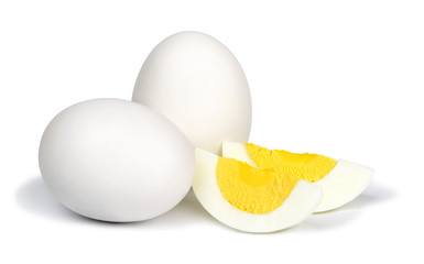 Two whole unpeeled boiled eggs and two slices of eggs isolated on a white background.