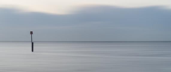Stunning sunrise landscape over rocks in sea