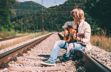 Young man with guitar sitting on the railway