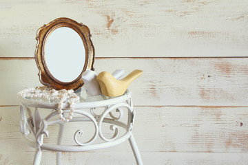 Antique blank vintage style frame, white pearls and couple of wooden birds on elegant table. template, ready to put photography