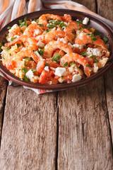 Greek cuisine: shrimp Saganaki on a plate. vertical