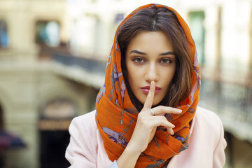 Portrait of attractive young woman with finger on lips