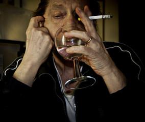 Uomo anziano con sigaretta e bicchiere