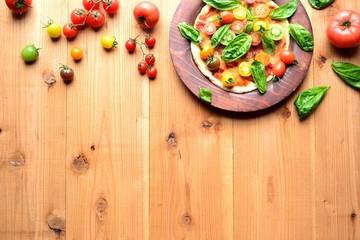 カラフルなトマトとバジルリーフのピザ