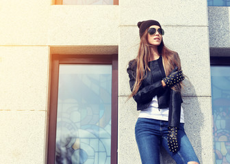 fashion model with long hair wearing sunglasses posing outdoor.