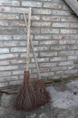 Brooms of branches on the brick wall background