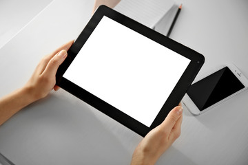Mobile phone and female hands using modern tablet, indoors
