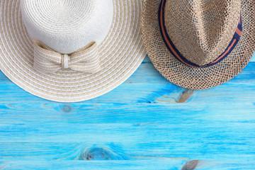 Summer hats on blue wooden background