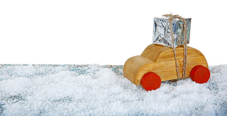 Wooden toy car with gift box on a snowy table over white ground