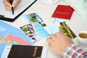 Passports with tickets, photos and world map at the table in the  office of travel company
