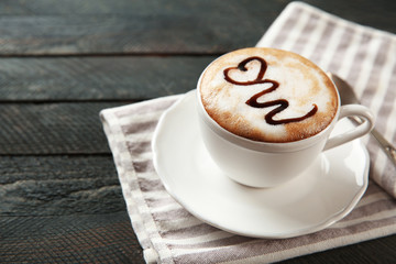 Cup of hot cappuccino with chocolate syrup and spoon on a black wooden table