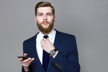 Bearded handsome man wearing smart suite on a gray background