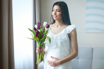 Pregnant woman with beautiful bouquet of tulips in the room