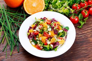 Fresh Orange, strawberry vegetables salad. on wooden table.