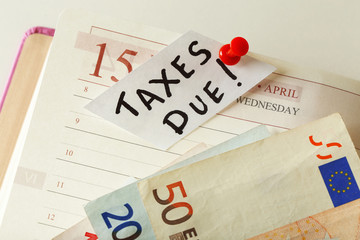 Taxes due  pinned in the planner with euro bills, close up