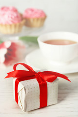 Present box with fresh tulips and cup of tea on wooden table closeup