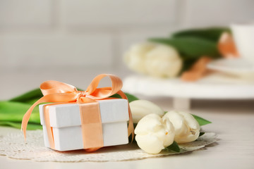 Bouquet of fresh tulips and present box on wooden table closeup