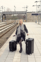woman standing with suitcases at train station