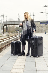 woman waiting with suitcases at train station