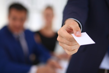 Closeup of a business man standing with card
