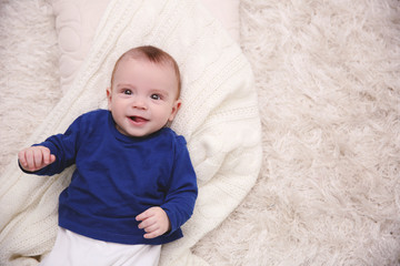 Portrait of adorable baby in blue pullover on the floor, close up