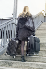 woman with suitcases walking up stairs