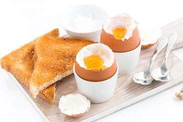 boiled eggs and crispy toasts on a wooden board, closeup