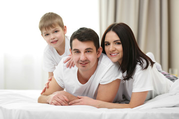 Portrait of happy family with mother, father and son lying in bed