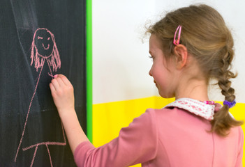 Cute little girl drawing a picture on blackboard.