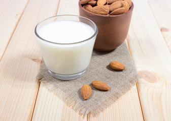 Almond milk with almond on a wooden table.
