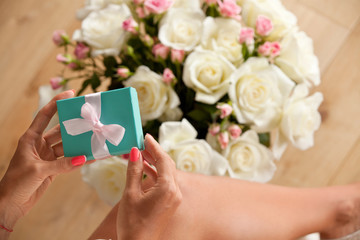 Gift box on woman hands and bouquet of beautiful roses.