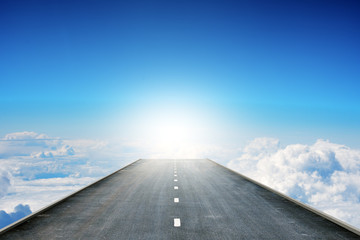 Road over clouds in sky