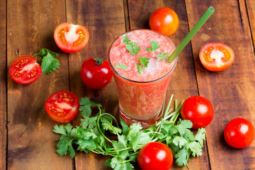 Gass of tomato smoothie, fresh tomatoes and cilantro on a dark wooden background . Vegetarian or healthy eating concept