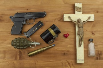Faith against violence. A wooden crucifix with the lettering INRI and guns. Faith and weapon defense of faith