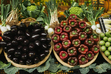 Fresh bell peppers and eggplants in baskets outside market sale