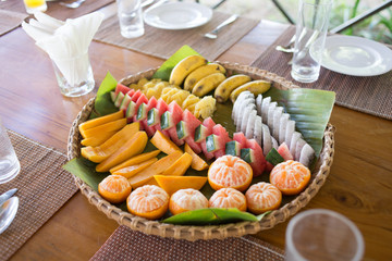 Wicker plate of tropical fruits in the middle of the wooden table