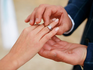Man making proposal with the ring to his girlfriend. Put ring on hand.