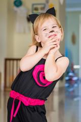 Cute little girl wearing black cat fancy dress. Preschool Halloween party.
