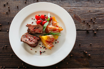 Wall Mural - Medium rare pork steak with fresh vegetables. Food photography of pork steak with potatoes and tomatoes cherry. Tasty cook meat with vegetables on dark wooden background.