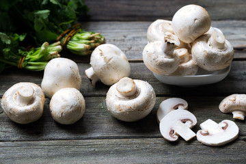 Fresh mushrooms champignons on wooden background