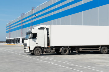 Loading dock of large warehouse with white truck under loading
