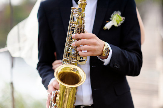 Hands of groom play on saxophone