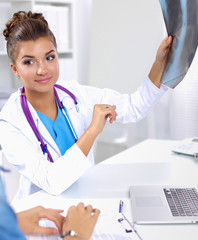 Young female doctor studying x-ray image sitting on the desk